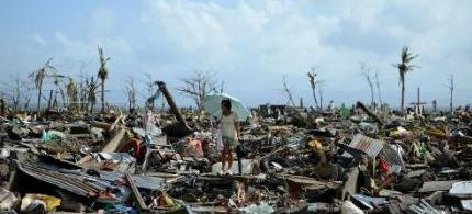 A survivor walks among the debris of houses destroyed by Super Typhoon Haiyan in Tacloban on the eastern Philippine island of Leyte on November 11, 2013. (photo: AFP/Noel Celis)