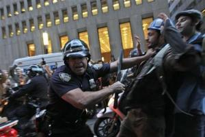 A New York City police officer shoves a  demonstrator affiliated with the Occupy Wall Street protests as they march through the streets in the Wall St. area, Friday, Oct. 14, 2011 in New York. (AP Photo/Mary Altaffer)