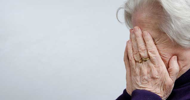 Elderly woman covers face