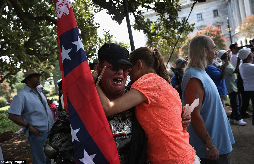 Protest: A woman clutching a Confederate flag during a KKK rally in South Carolina wails as emotions run high