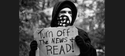 An Occupy protester urges peoples to turn off the news and read. (photo: Possible Futures)