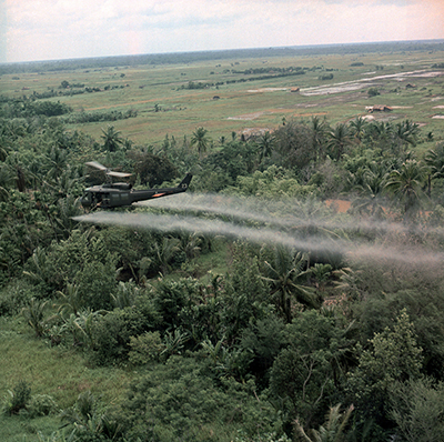 A helicopter sprays foliage with Agent Orange in an undated photo taken during the Vietnam War. (Photo via Shutterstock)