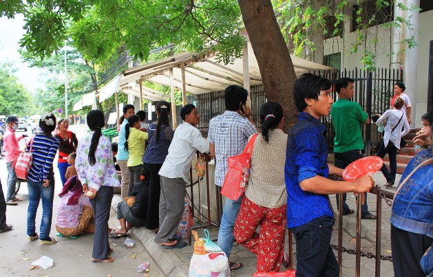 Parents wait anxiously outside a Phnom Penh hospital. Credit: Vincent McIsaac/IPS