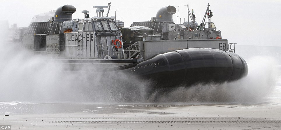 Fast response: A Navy LCAC hovercraft lands on the beach in Camp Lejeune as the simulated amphibious assault swings into action