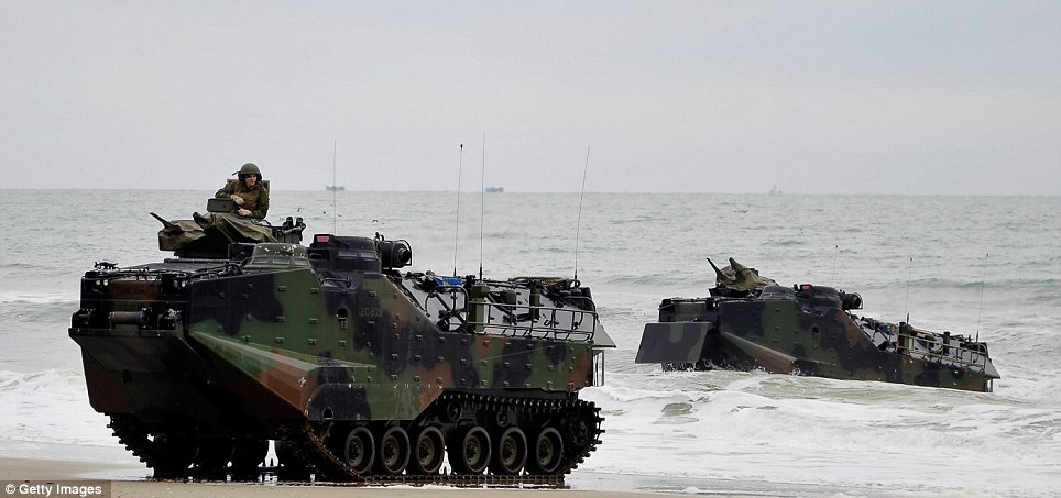 Getting wet: Amphibious vehicles, with a soldier manning the guns, drive out of the surf with other warships in the background