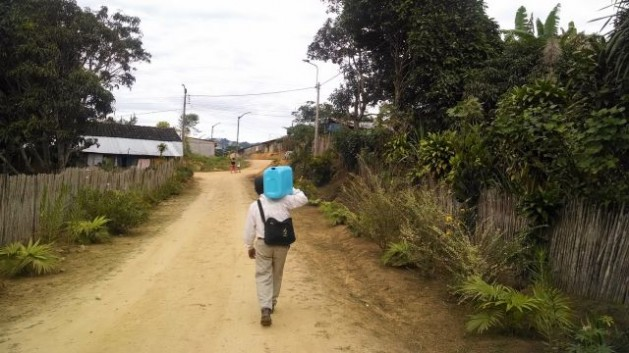 "A Jepelacio resident carries a blue jerrycan with 20 litres of ""Jepe water"" along one of the dusty but clean streets of this town in the Peruvian Amazon, a healthful routine many families carry out daily. Credit: Milagros Salazar/IPS"