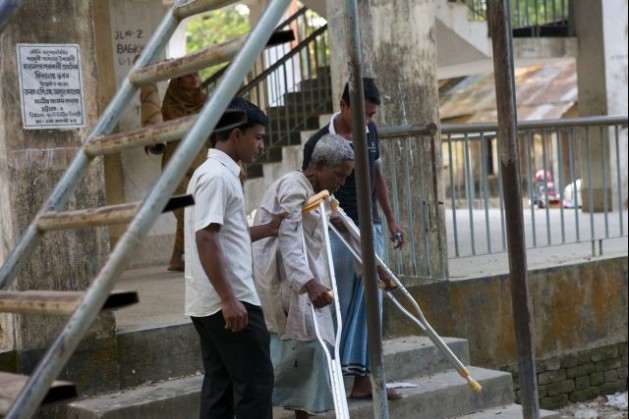 Disaster Risk Management Project (DRM). An elderly person with a disability goes down the stairs of the Cyclone shelter in Mohanagar, Sitakunda, Bangladesh. Credit: Brice Blondel/Handicap International