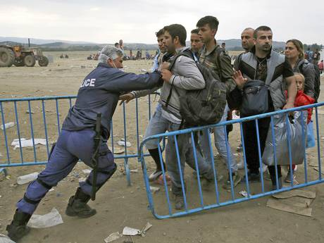 A policeman pushes refugees behind a barrier at Greece's border with Macedonia, near the village of Idomeni