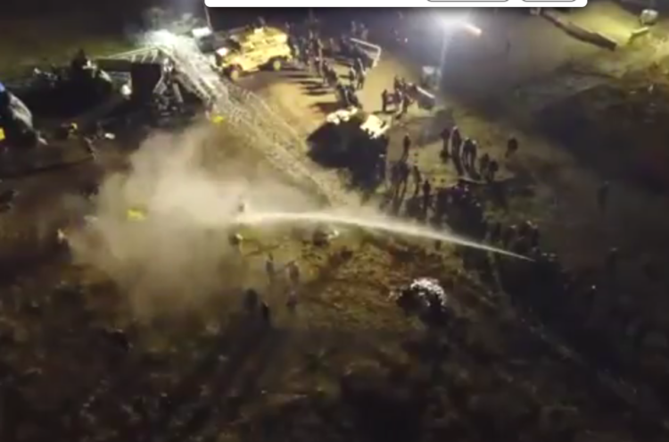 Drone footage captures police spraying Dakota Access Pipeline protesters with a water cannon.
